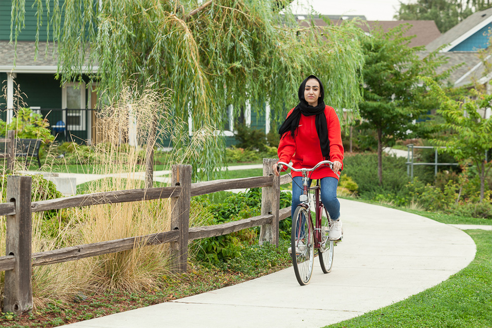 Woman riding bicycle alongside greenery